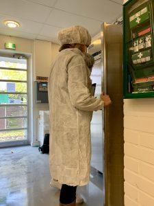 Valkoiseen suojatakkiin pukeutunut henkilö katsoo jääkaappiin
