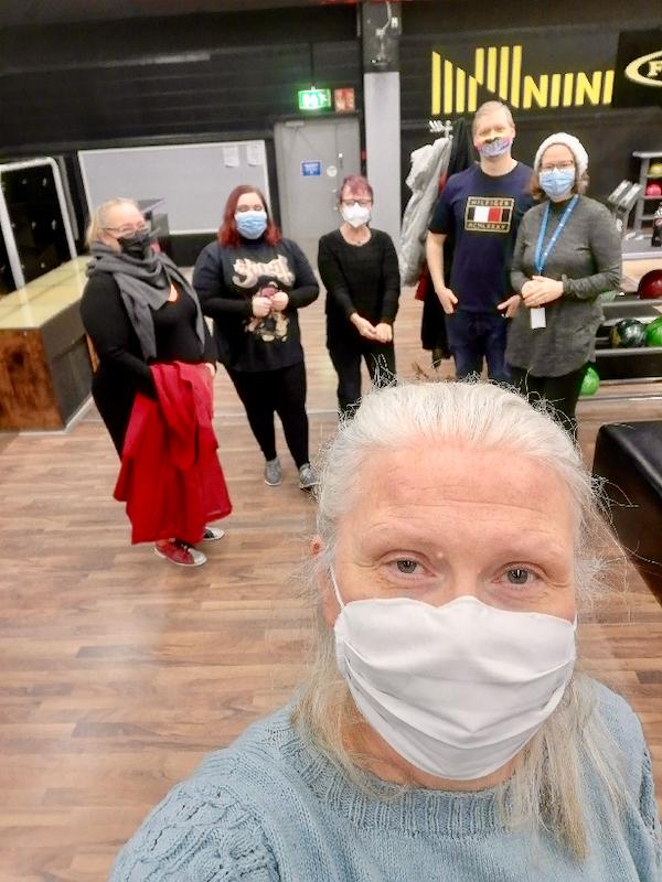 Ryhmä keilahallin radan edessä maskit kasvoilla